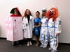 Five people lined up in a row and wearing costumes. From left to right, they are wearing: a makeshift, handdrawn-looking rocket ship, a whitecoat, a dress that has a space pattern, and two astronauts.